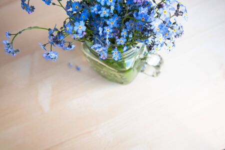 bouquet of forget-me-not flowers in a glass cup on an unfocused background Foto de archivo