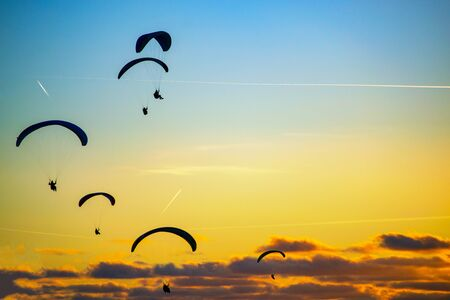 silhouettes of a paragliders flying in the sky at sunset Foto de archivo