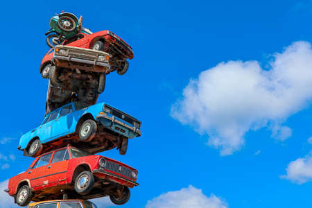 Stack of old cars against a blue sky