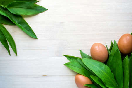 Leaves of a ramson and chicken eggs, fresh raw wild garlic on light wooden background Foto de archivo