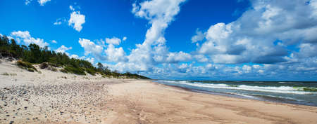 Panorama of sand dunes, sea waves and blue sky in a summer morning