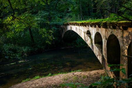 old abandoned bridge over a forest river Banque d'images - 158326447