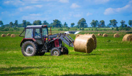 Tractor carrying hay bale rolls and collecting them on a field.
