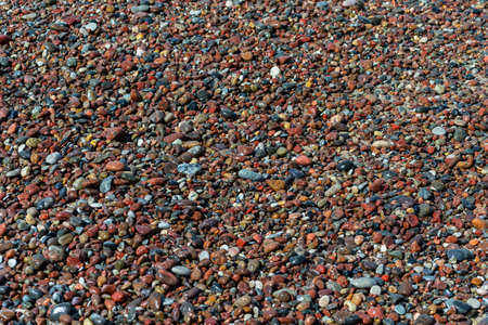 Wet pebbles on a sea shore. Natural background