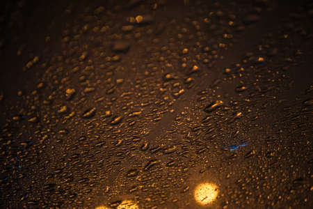natural drops of water on glass, night photo with a street lights outside