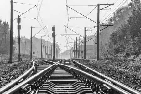 Two railway tracks with electric power poles near a small train station Banque d'images - 158834531