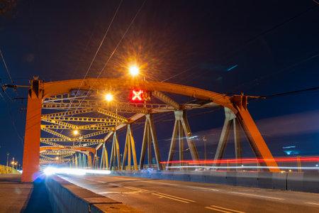 Orange road bridge with reverse traffic, night photo Banque d'images