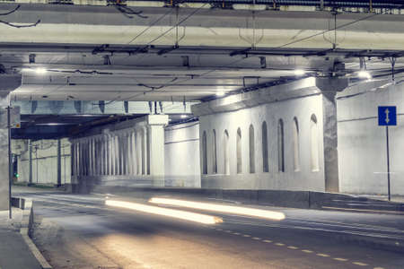 Night city street under the bridge, road with a reverse motion with an information sign