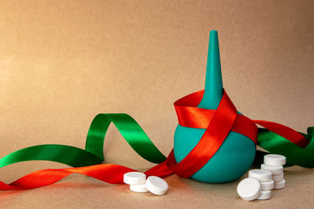 medical holiday background with ribbons, rubber bulb syringe and white tablets Banque d'images - 160182881