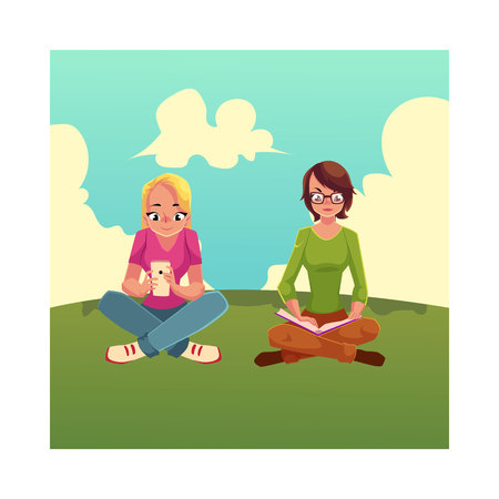 Two girls siting crossed legs, one reading book on the grass, another using mobile phone. Zdjęcie Seryjne - 81013031
