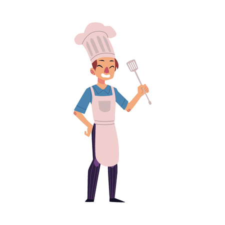 Full-length portrait of a happy young Caucasian chef in hat and apron holding kitchen turner.