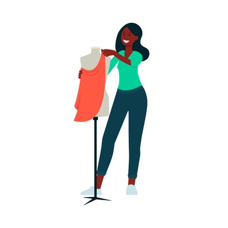Donna afro-americana in piedi vicino al manichino e attaccando il tessuto ad esso in stile cartone animato, illustrazione vettoriale isolato su sfondo bianco. Stilista che fa un vestito o un altro indumento di vestiti Vettoriali
