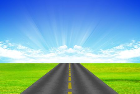 clean street: Road with yellow dividing stripon background of green grass and blue sky Stock Photo