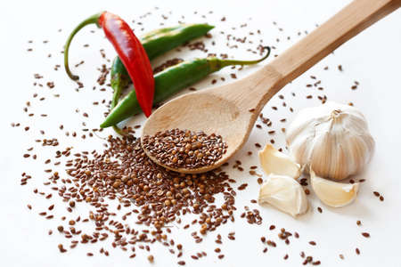 Cayenne peppers, flax seeds, coriander and garlic on white background photo