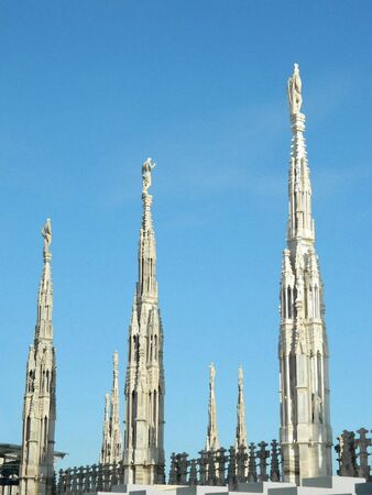 spires: Three Milan Duomo spires with statues on top representing saints or warriors, roman gladiators or soldiers with helmet and cape.