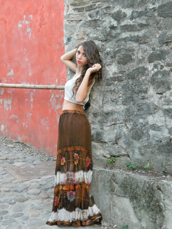 gipsy: Beautiful young woman,posing in city of Sighisoara, Romania, expressive, with white top and long brown decorated gipsy skirt.