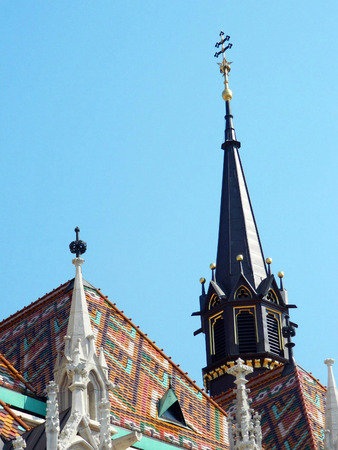 castle district: Matthias Church closeup, spires and towers, Hungarian: Mtys-templom is a Roman Catholic church located in Budapest, Hungary, in front of the Fishermans Bastion at the heart of Budas Castle District. According to church tradition, it was originally built