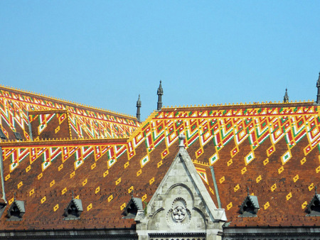 castle district: Matthias Church closeup,colored roof, Hungarian: Mtys-templom is a Roman Catholic church located in Budapest, Hungary, in front of the Fishermans Bastion at the heart of Budas Castle District. According to church tradition, it was originally built in Ro