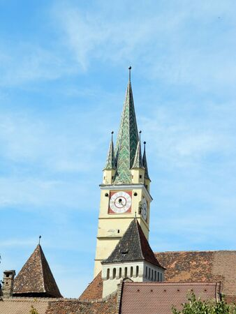 imposing: Medias, Transylvania. Cityscape of downtown in medieval city with fortified church tower, landmark in Romania, and imposing Saxon Tower.