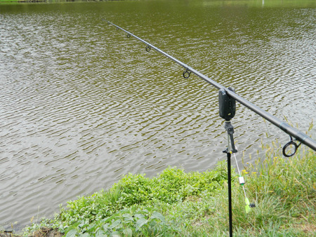 Fishing pole: Fishing pole launched in lake. Stock Photo