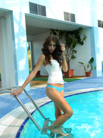 Beautiful and attractive female model posing by the pool in white top and blue bikini.