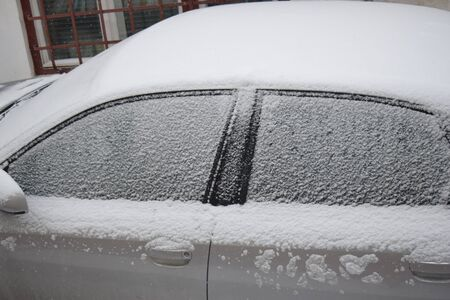 Car covered with white snow while still snowing in Medias, Romania. Stock Photo