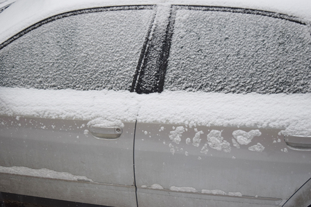 downfall: Car covered with white snow while still snowing in Medias, Romania. Stock Photo