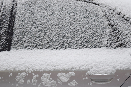 Car body part covered with white snow while still snowing in Medias, Romania.