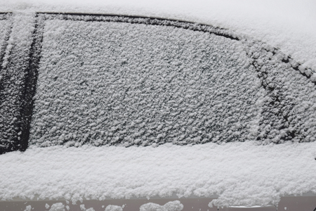 Car body part covered with white snow while still snowing in Medias, Romania. Stock Photo - 51356089