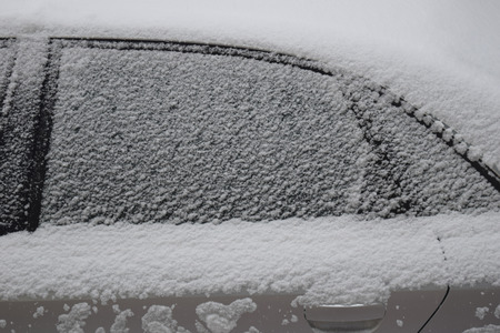 Car body part covered with white snow while still snowing in Medias, Romania. Stock Photo - 51356108