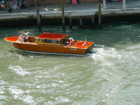 VENICE, ITALY - 6 JULY 2015 Wooden Venice taxi motorboat with passengers water taxi in Grand Canal Stock Photo - 55334619