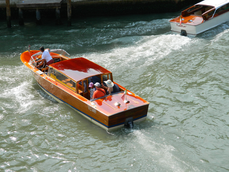 VENICE, ITALY - 6 JULY 2015 Wooden Venice taxi motorboat with passengers water taxi in Grand Canal