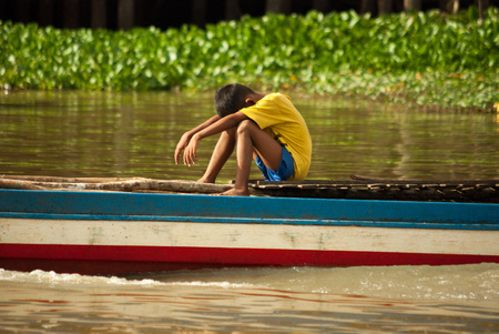 Boy resting in a boat on the Tonle Sap close to Siem Reap Cambodia Archivio Fotografico
