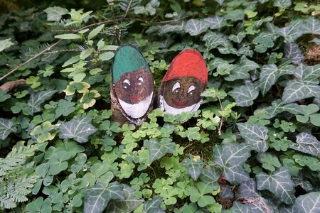 Tinkered wooden gnomes in the forest between clovers