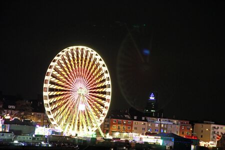 Illuminated Ferris wheel in the dark at a folk festival. The Ferris wheel is a bike-shaped ride at folk festivals that lifts fellow cyclists on its perimeter to a position with good views