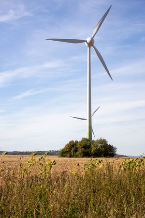 Two wind turbines in a row on a sunny autumn day