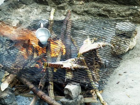 Preparing a food on a grid over a campfire