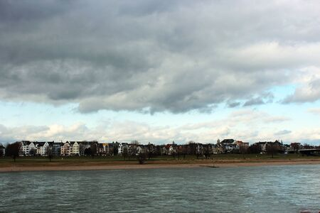 View over the Rhine to a residential area in Dusseldorf on a cloudy day, Germany