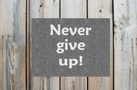 persistence: Motivational message Never give up on wooden background