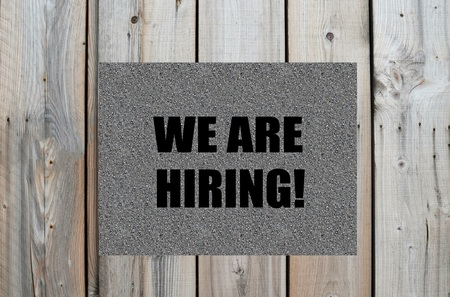 we: We are hiring text on wooden background