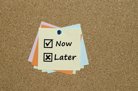 postpone: Now and later check boxes on paper note over  cork board