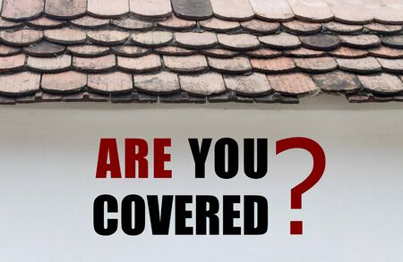 home protection: Are you covered text written over old house wall Stock Photo