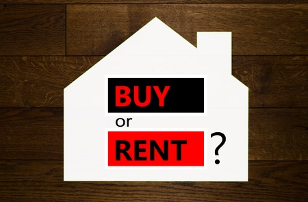 Buy or rent a house question over wooden background