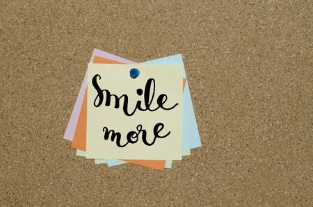 clavados: Sonreír más texto letras de la mano en la nota de papel fija a bordo de corcho