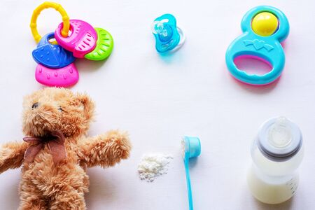 Baby milk powder, baby bottle and children's toys on a light background