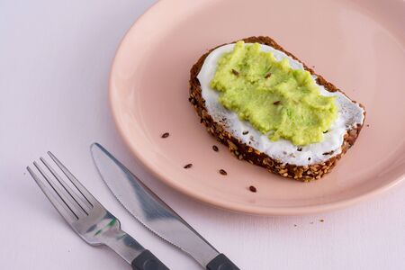 Sandwich with black rye bread and avocado mousse