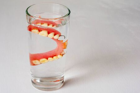 denture in a glass with water on a white background Banque d'images - 127534284