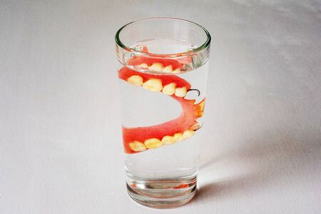 denture in a glass with water on a white background. Banque d'images - 127534044