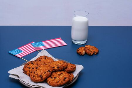 Chocolate breakfast cookies with a glass of milk on a turquoise table. Patriotic breakfast concept - happy presidents day. Banco de Imagens