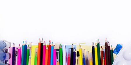 A lot of multi-colored school and office supplies on a white background - Banner. Back to school. Copyspace for text. Banco de Imagens